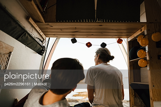 Rear view of male friends spending leisure time in motor home - p426m2296161 by Maskot