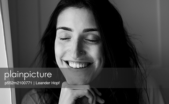 Happy woman with dark hair - p552m2100771 by Leander Hopf
