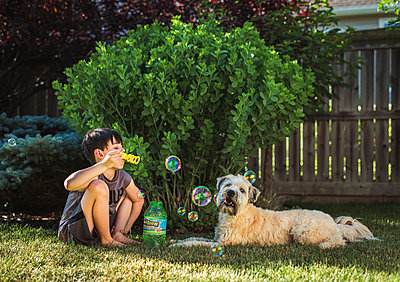 Young boy blowing bubbles for his dog in a backyard on a summer day. - p1166m2138081 by Cavan Images