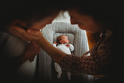 Mom and dad holding hands looking at newborn baby sleeping - p1166m2290202 by Cavan Images
