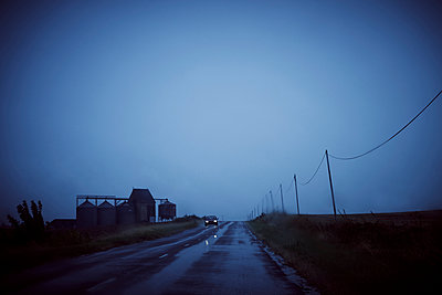 View through windshield of a car on country road with oncoming traffic at dusk - p1312m2229774 by Axel Killian