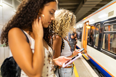 UK, London, two young women with cell phones waiting at underground station platform - p300m2063022 by William Perugini