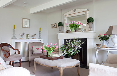 Cut flowers and ottoman at fireplace in Sussex home  UK - p3493564 by Robert Sanderson