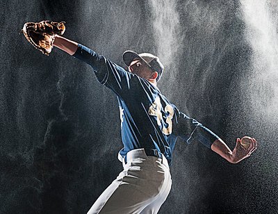 Caucasian baseball player pitching in rain - p555m1454264 by Erik Isakson