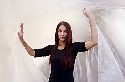 Portrait of young woman standing under plastic sheet - p577m2038715 by Mihaela Ninic