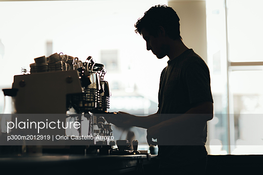 Silhouette of Barista preparing coffee in a coffee bar - p300m2012919 von Oriol Castelló Arroyo