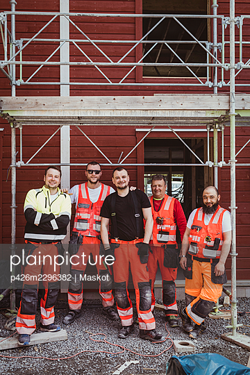 Full length of male construction workers standing together at site - p426m2296382 by Maskot