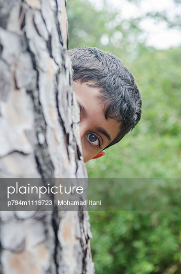 Boy hiding behind a tree  - p794m1119723 by Mohamad Itani