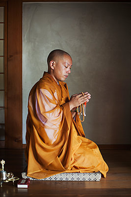 Side view of Buddhist monk with shaved head wearing golden robe kneeling indoors in a temple, holding mala, praying. - p1100m1531012 by Mint Images