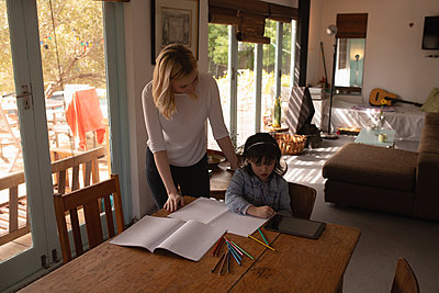 Mother helping her daughter with homework - p1315m2056249 by Wavebreak