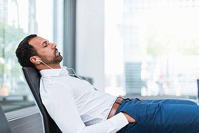 Businessman with earphones, closed eyes - p300m1587897 von Daniel Ingold