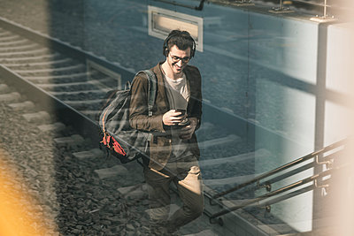 Smiling young man with headphones, cell phone and takeaway coffee walking at the station - p300m2104467 by Uwe Umstätter