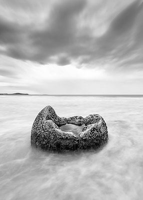 Moeraki Boulder in sea at Koekohe Beach against cloudy sky, New Zealand - p300m2144338 by Scott Masterton