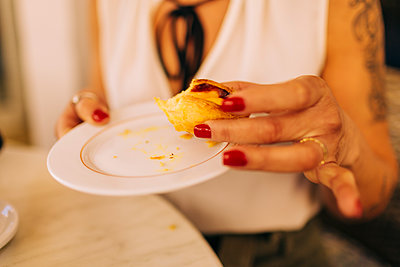 Close-up of mid adult woman holding food in plate at restaurant - p300m2202469 by Alexandra C. Ribeiro