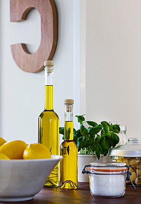 Olive oil and lemons in domestic kitchen - p312m695920 by Hans Bjurling