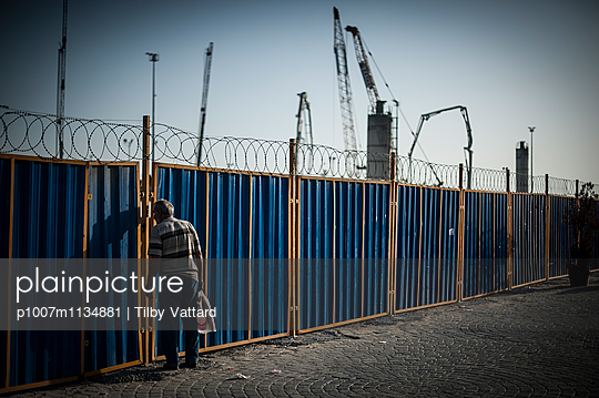 Man looking through the fence of a construction site - p1007m1134881 by Tilby Vattard