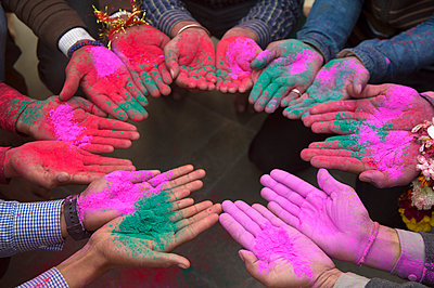 High angle view of people standing in circle, holding up their palms covered in bright pink and green paint. - p1100m1570874 by Mint Images