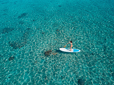 High angle view of woman paddleboarding on sea - p1166m1554265 by Cavan Images