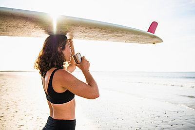 Woman Enjoying Morning Coffee before Surf - p1166m2261724 by Cavan Images