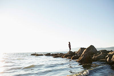 Pensive woman standing on rocks looking at sunny ocean view - p1192m1511914 by Hero Images