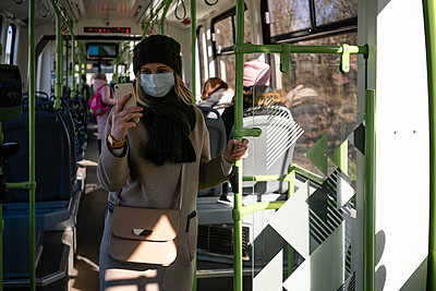 Woman with face mask using smartphone in tram - p300m2170847 by Vasily Pindyurin