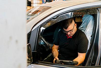 Mechanic examining car while sitting on vehicle seat in garage - p300m2220816 by Ezequiel Giménez