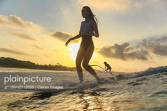 Female surfer in ocean at sunset - p1166m2112035 by Cavan Images