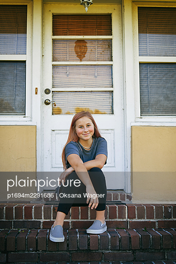 Happy girl with crossed arms sitting on the steps in front of the entry door - p1694m2291686 by Oksana Wagner