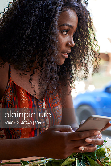 Portrait of young African woman in a cafe, checking her smartphone - p300m2140740 by Veam