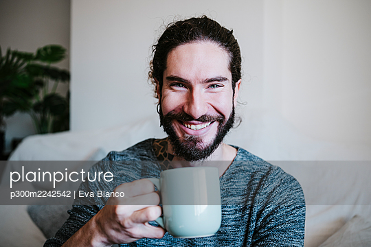 Young man smiling while drinking coffee sitting at home - p300m2242542 by Eva Blanco