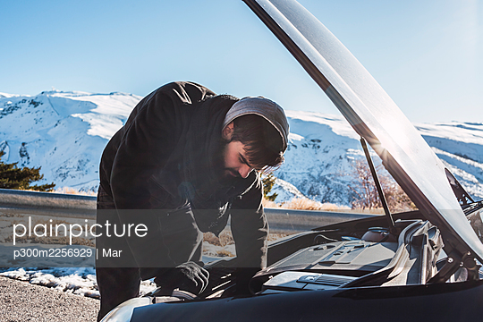 Man repairing car on snow covered land against sky during winter - p300m2256929 by Mar