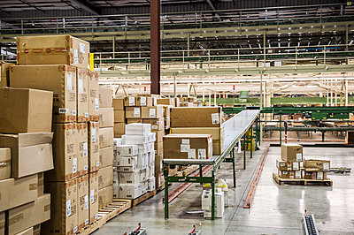Conveyor belt system and cardboard boxes of products in a distribution warehouse. - p1100m2002286 by Mint Images