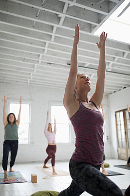 Focused woman practicing yoga warrior one pose in yoga class - p1192m1583324 by Hero Images