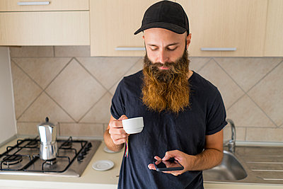 Bearded man standing in kitchen with espresso cup looking at cell phone - p300m1581187 von VITTA GALLERY
