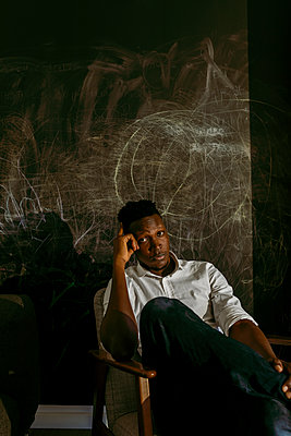 Worried businessman sitting on chair against scribble wall - p300m2241200 by Valentina Barreto