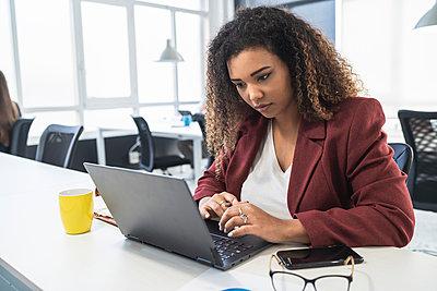 Businesswoman working on laptop at desk in office - p300m2282785 by SERGIO NIEVAS