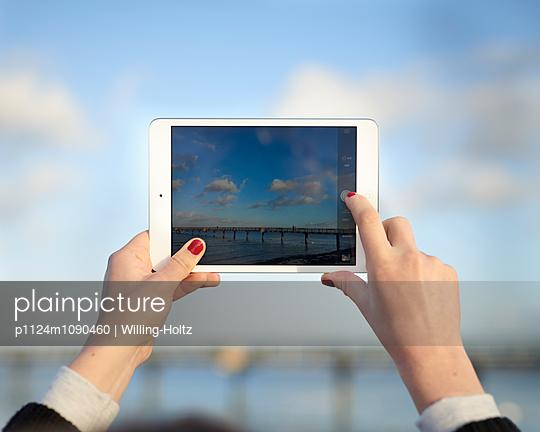 Frau fotografiert Seebrücke mit Ipad - p1124m1090460 von Willing-Holtz
