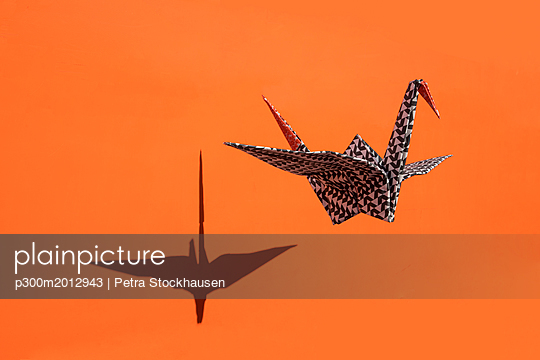 Origami crane, orange background, shadow, copy space - p300m2012943 von Petra Stockhausen