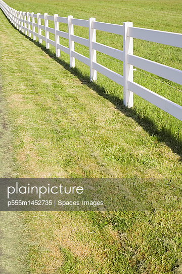 A long white farm fence in countryside surrounding pasture