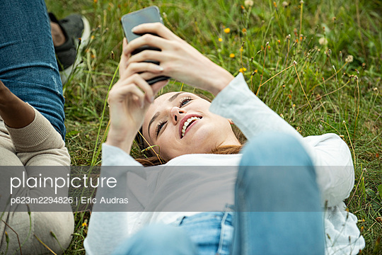 Young female friends lying on grass while using smart phone in park - p623m2294826 by Eric Audras