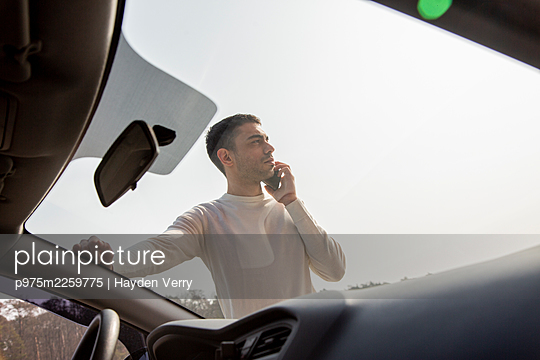 Young man makes phone calls next to his car - p975m2259775 by Hayden Verry