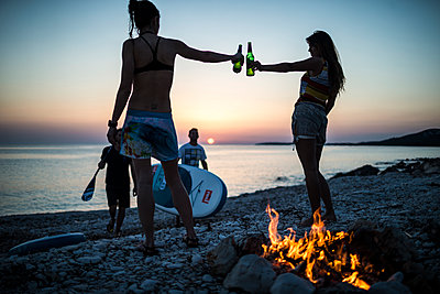 A group of young people gathered on a beach by a campfire. - p1100m1482334 by Mint Images