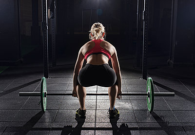 Rear view of woman picking barbell at gym - p1166m1154113 by Cavan Images