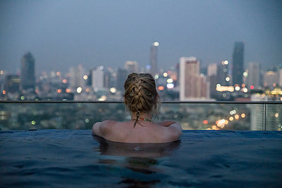 Thailand, Bangkok, back view of woman bathing in Infinity Pool looking at skyline - p300m2012466 by Christophe Papke