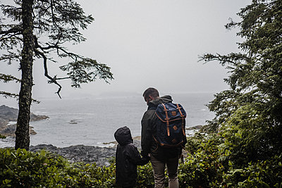 Father and child looking out to sea, Tofino, Canada - p924m2018498 by Kymberlie Dozois Photography