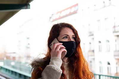 Deutschland, Berlin, Junge Frau mit Mundschutz und Smartphone, Portrait - p975m2223630 von Hayden Verry