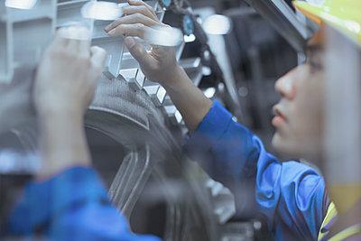 Engineer repairing machinery in factory - p1023m1105808f by Martin Barraud