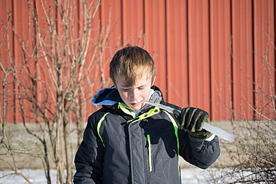 Boy eating icicle outdoors - p1169m2108449 by Tytia Habing