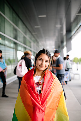 Portrait of young woman on gay pride wrapped in rainbow flag - p1192m2110162 by Hero Images