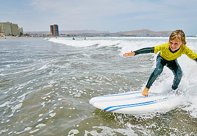 Chile, Arica, happy boy surfing in the sea - p300m2069123 by Stefan Schütz